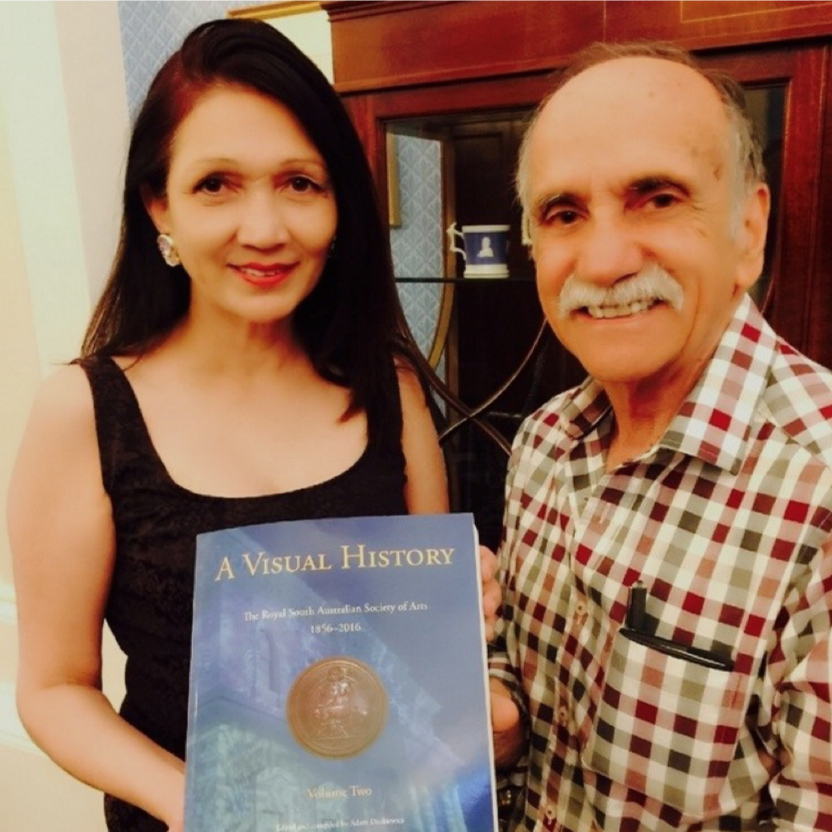 """The Lady Mayoress Genevieve Theseira holding the second edition of """"A Visual History of the Royal South Australian Society of Arts"""" with Jack Condous"""